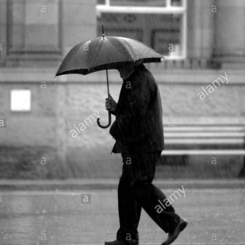 wimbourne-un-uomo-cammina-lungo-la-strada-sotto-la-pioggia-battente-con-un-ombrello-d0ppg6